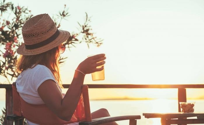 woman sitting holding drink looking at sunset