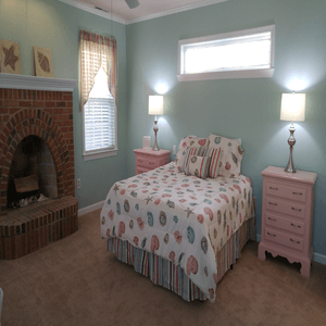 bedroom with one bed two end tables and fireplace