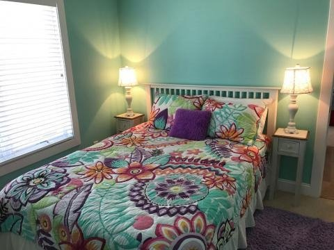 small bedroom with light green walls queen bed