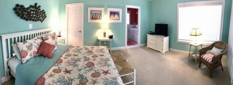 master bedroom with queen bed light blue walls window and private bathroom